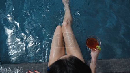 top view of wet woman in swimsuit sitting near pool with cocktail