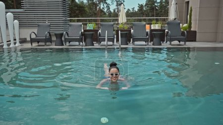 Photo for Happy young woman in sunglasses swimming in outdoor pool - Royalty Free Image