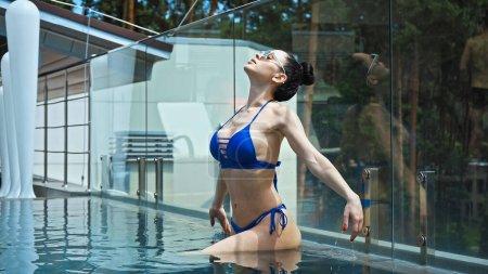 morena mujer en gafas de sol con los ojos cerrados de pie en la piscina al aire libre