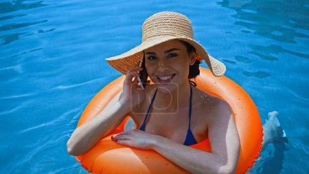 Photo pour Femme heureuse nageant dans la piscine avec anneau gonflable et parlant sur le smartphone - image libre de droit
