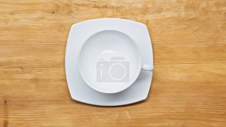 top view of white, empty cup and saucer on wooden surface