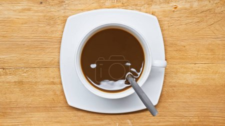 top view of cocoa drink in white cup on wooden table
