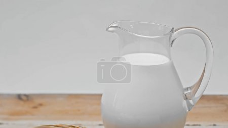 glass jar full of fresh milk on wooden surface isolated on grey