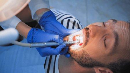 Photo pour Dentiste traitant les dents du patient avec une perceuse dentaire, avant-plan flou - image libre de droit