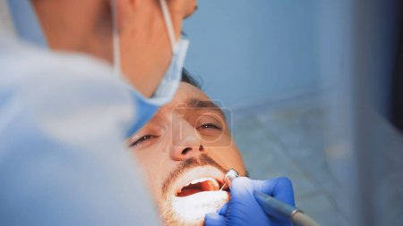 stomatologist in medical mask using dental drill on patient, blurred foreground