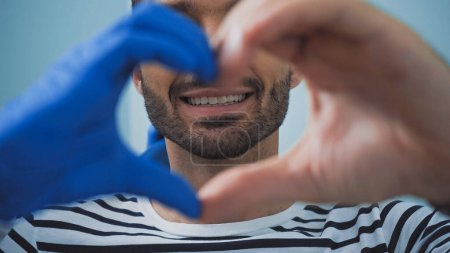 partial view of man and dentist showing heart symbol with hands, blurred foreground