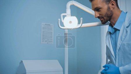 Photo pour Dentiste positif en manteau blanc et gants en latex près de la lampe sur le lieu de travail - image libre de droit