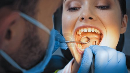 stomatologist in medical mask examining teeth of woman, blurred foreground