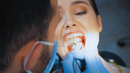 dentist in medical mask using dental drill while treating teeth of woman, blurred foreground
