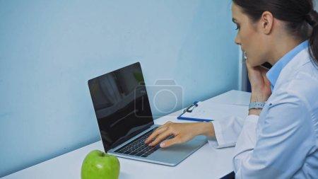 stomatologue tapant sur ordinateur portable et parlant sur smartphone près de pomme fraîche et presse-papiers