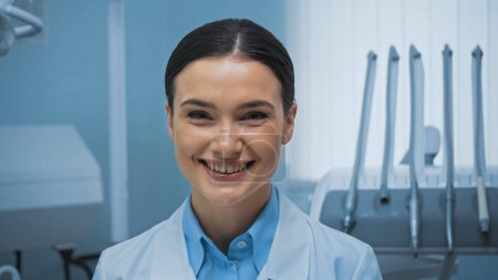 cheerful dentist smiling at camera near dental equipment on blurred background