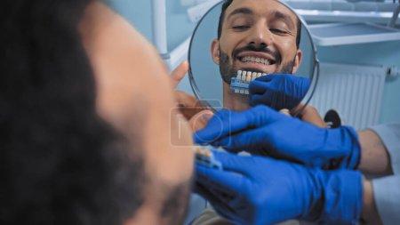 stomatologue tenant la palette de couleurs des dents près d'un patient souriant, avant-plan flou