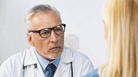Photo pour Médecin dans les lunettes écouter la femme lors d'un rendez-vous à la clinique, avant-plan flou - image libre de droit