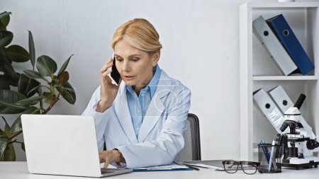mature doctor talking on smartphone near laptop at workplace