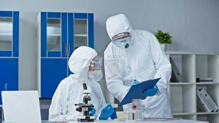 scientist in hazmat suit showing research results to colleague in laboratory