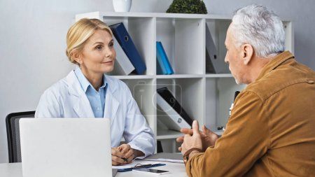 mature man talking to smiling doctor during consultation in clinic