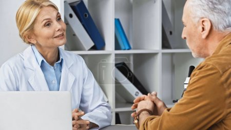 positive doctor talking to man during appointment in hospital