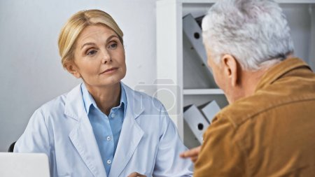 attentive doctor listening to man during consultation in hospital, blurred foreground