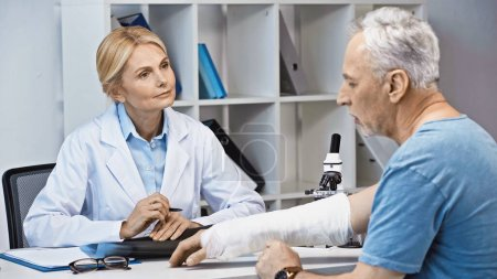 attentive doctor listening to man with broken arm in consulting room