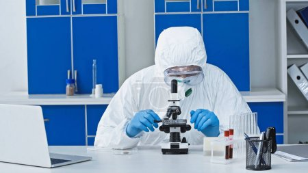 virologist in hazmat suit doing working with microscope near laptop in laboratory