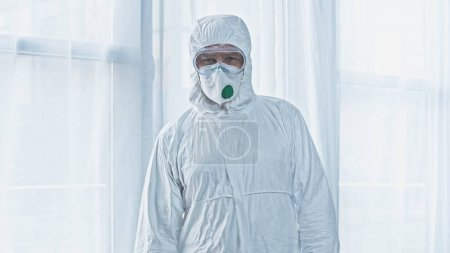 virologist in hazmat suit looking at camera while standing near window