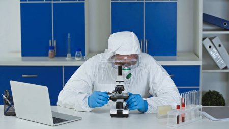scientist working with microscope near laptop in laboratory