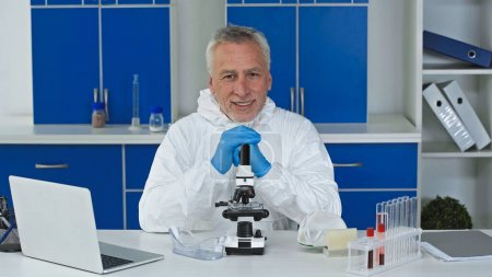 smiling scientist in hazmat suit looking at camera near microscope and laptop