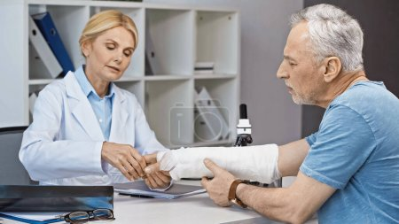Photo for Traumatologist examining broken arm of mature man in hospital - Royalty Free Image