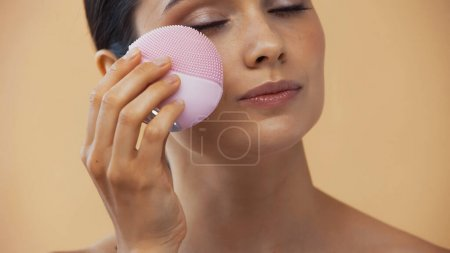 Photo for Pretty woman using silicone cleanser with closed eyes isolated on beige - Royalty Free Image