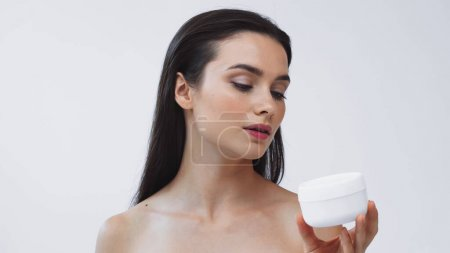 young woman with healthy skin holding cosmetic cream isolated on grey