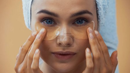 close up view of young woman applying eye patches isolated on beige