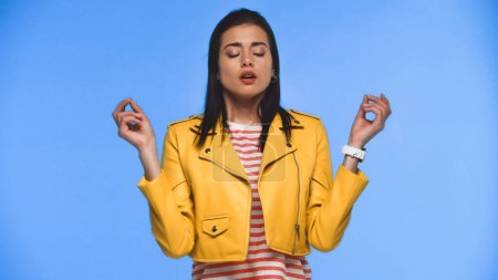 Photo for Young woman in yellow jacket meditating isolated on blue - Royalty Free Image