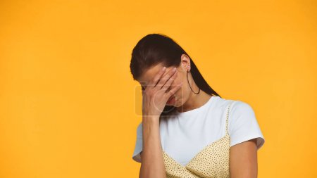Displeased woman covering face with hand isolated on yellow