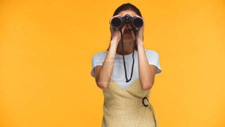 Foto de Mujer mirando a través de prismáticos aislados en amarillo - Imagen libre de derechos