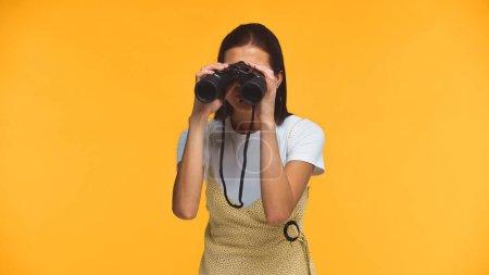 Foto de Mujer joven mirando a través de prismáticos aislados en amarillo - Imagen libre de derechos