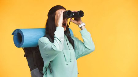 Excited traveler with backpack looking through binoculars isolated on yellow