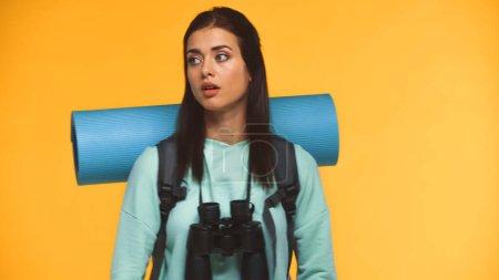 Photo pour Voyageur perdu avec sac à dos, tapis de fitness et jumelles regardant loin isolé sur jaune - image libre de droit