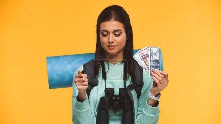 Photo pour Voyageur avec sac à dos tenant briquet brûlant près de l'argent isolé sur jaune - image libre de droit