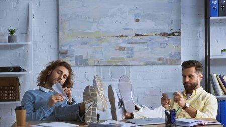 Photo pour Jeunes hommes d'affaires assis avec les jambes sur le bureau tout en ayant du repos au bureau - image libre de droit