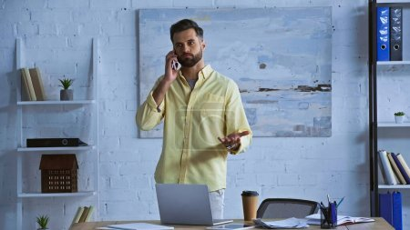 discouraged businessman talking on cellphone while standing in office