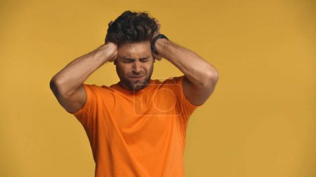 man touching head while suffering from migraine isolated on yellow