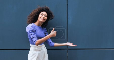 cheerful young woman pointing with hand and showing thumb up outside