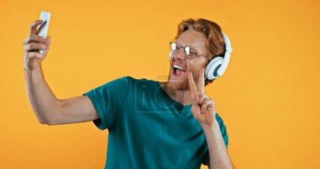 Photo pour Homme rousse étonné dans les écouteurs sans fil prenant selfie tout en montrant signe de paix isolé sur jaune - image libre de droit