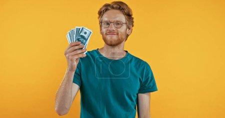 Photo pour Heureux rousse homme tenant dollars isolé sur jaune - image libre de droit