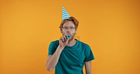 redhead man in party cap blowing in party horn isolated on yellow