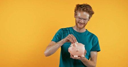 glücklicher Rotschopf legt Münze in Sparschwein isoliert auf gelb