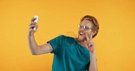 Erstaunter Mann zeigt Friedenszeichen, während er ein Selfie macht