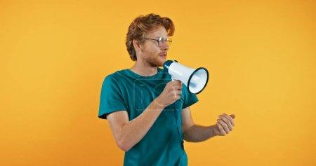 Photo pour Rousse homme à lunettes tenant mégaphone isolé sur jaune - image libre de droit