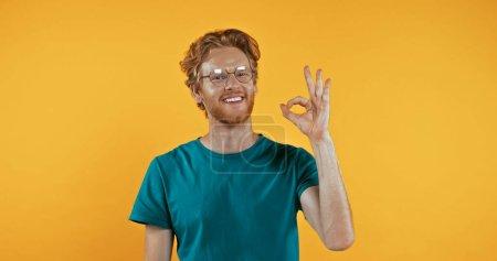 Photo pour Rousse positive homme dans des lunettes montrant signe OK isolé sur jaune - image libre de droit