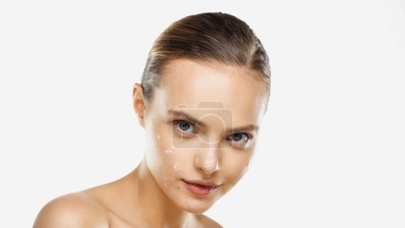 sensual young woman with bare shoulders and cream on face looking at camera isolated on white